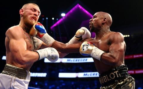Floyd Mayweather Jr. lands a hit against Conor McGregor during a boxing match at T-Mobile Arena - Credit: USA TODAY SPORTS