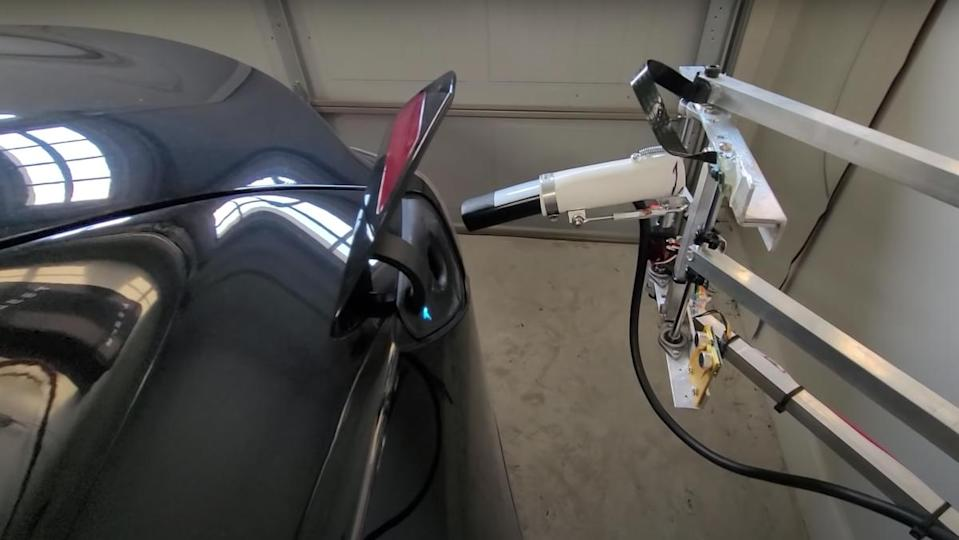 A Tesla home charger automatically inserting itself into a Tesla Model 3 vehicle.