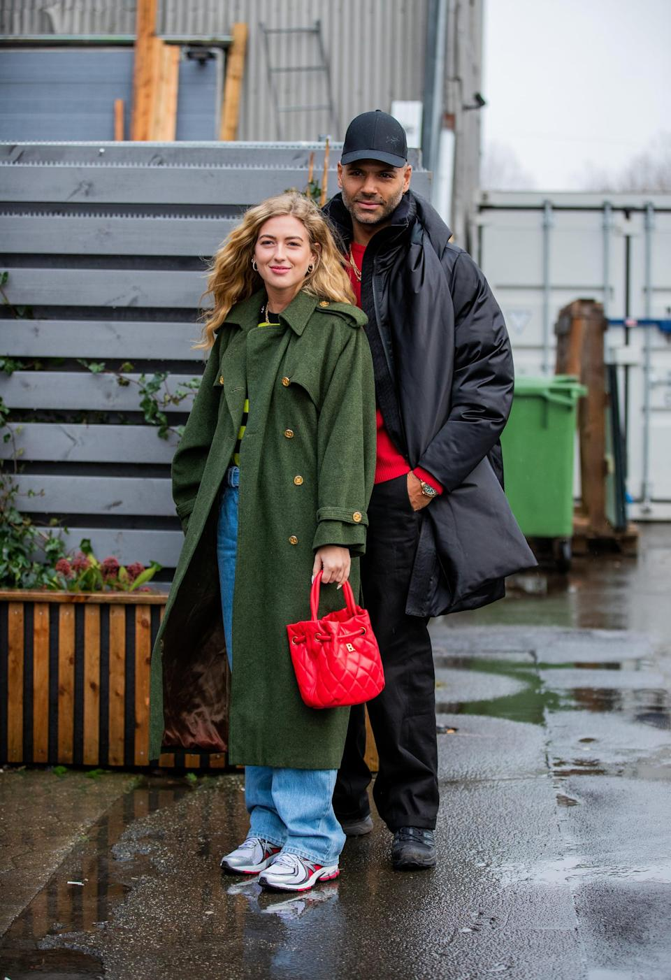 """<p>For chic """"dad"""" vibes, team a pair of slouchy straight-leg jeans with running sneakers, a trench coat, and a bright bag. </p>"""