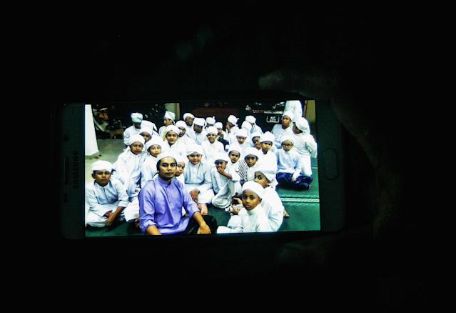 <p>A resident shows a pictures of some of the student in religious school Darul Quran Ittifaqiyah before a fire broke out early morning on his smartphone on Sept. 14, 2017 in Kuala Lumpur, Malaysia. (Photo: Mohd Samsul Mohd Said/Getty Images) </p>