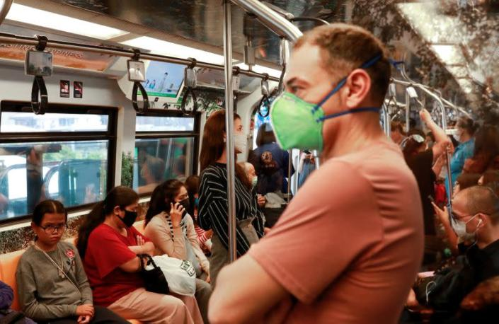 Passengers wear protective masks due to the coronavirus outbreak, in a train in Bangkok