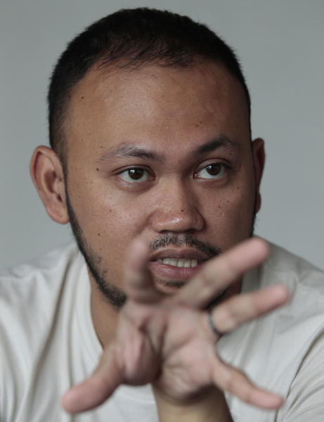 "In this photo taken on May 8, 2013, Filipino director Borinaga Alix Jr. gestures during an interview inside his home in suburban Quezon city, north of Manila, Philippines. Alix could have shot his film ""Death March"" on location in a large-scale production, but instead chose to film it in black-and-white and almost entirely inside a studio using hand-painted backdrops, with close-ups of actors' painted faces portraying their struggles with nightmares and hallucinations in one of the bloodiest episodes of World War II. (AP Photo/Aaron Favila)"