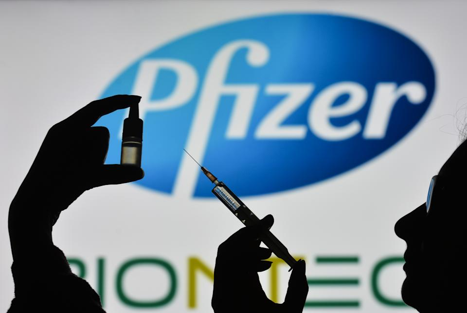 IRELAND - 2021/02/07: In this photo illustration a silhouette of a man holding a medical syringe and a vial seen displayed in front of the Pfizer logo on a screen. (Photo Illustration by Cezary Kowalski/SOPA Images/LightRocket via Getty Images)