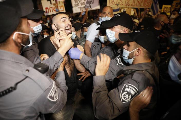"""Israeli police officers push a protester outside Prime Minister's residence in Jerusalem, Tuesday, July 14, 2020. Thousands of Israelis on Tuesday demonstrated outside the official residence of Prime Minister Benjamin Netanyahu, calling on the embattled Israeli leader to resign as he faces a trial on corruption charges and grapples with a deepening coronavirus crisis. The signs reads """"You are detached. We are fed up"""".(AP Photo/Ariel Schalit)"""