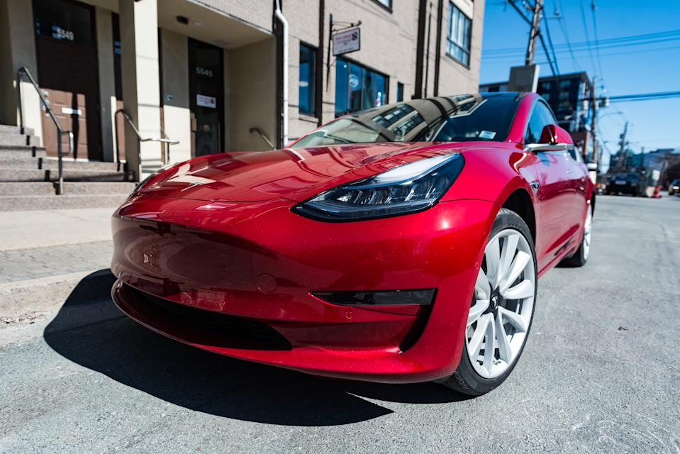 March 26, 2019 - Halifax, Canada - A 2019 red Tesla Model 3 plug-in electric car parked on a city street in downtown Halifax.