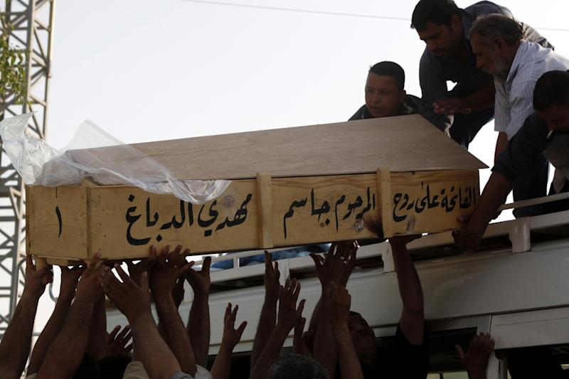 FILE - In this Wednesday, June 13, 2012, file photo, family members of Bilal Aziz, 20, who was killed in a car bomb attack, load his coffin onto a vehicle before burial in Najaf, Iraq. June was the second-deadliest month since U.S. troops withdrew from Iraq in mid-December, but more significant than the numbers was the fact that insurgents appeared able to sustain the level of violence over a longer period than usual. (AP Photo/Alaa al-Marjani, File)