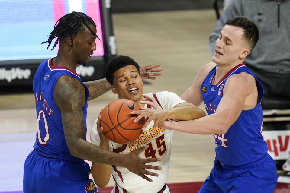 Iowa State guard Rasir Bolton, center, looks to pass between Kansas guard Marcus Garrett, left, and forward Mitch Lightfoot, right, during the second half of an NCAA college basketball game, Saturday, Feb. 13, 2021, in Ames, Iowa. Kansas won 64-50. (AP Photo/Charlie Neibergall)
