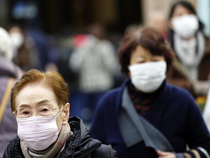 Pedestrians wear protective masks as they walk through a shopping district in Tokyo Thursday Jan 16 2020: AP