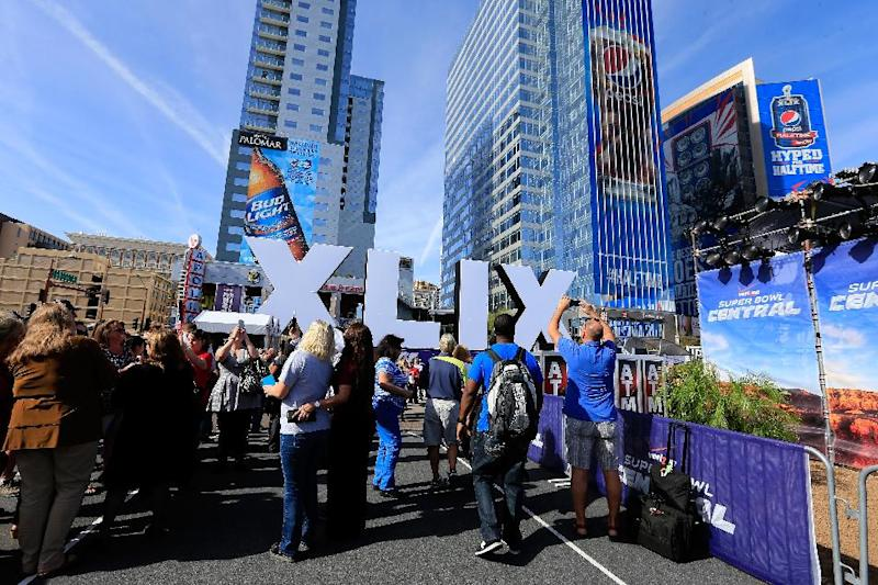 People walk past the logo for the upcoming Super Bowl XLIX between the Seattle Seahawks and New England Patriots on January 28, 2015 in Phoenix, Arizona (AFP Photo/Rob Carr)