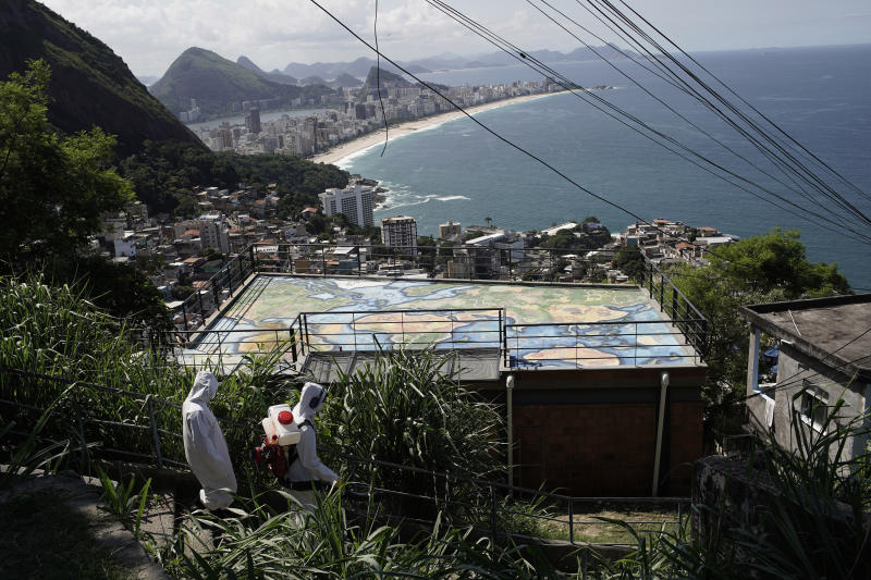 Water utility workers from CEDAE disinfect in the Vidigal favela, which overlooks the oceanfront Leblon and Ipanema neighborhoods, in an effort to curb the spread of the new coronavirus, in Rio de Janeiro, Brazil, Friday, April 24, 2020. (AP Photo/Silvia Izquierdo)