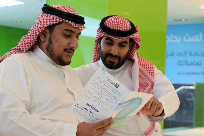 Saudi men check the prospectus of Aramco IPO, in Riyadh