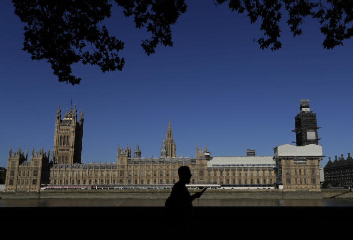 A pedestrian passes Britain's Houses of Parliament on the bank of The River Thames in London, Thursday, Aug. 29, 2019. Jacob Rees-Mogg, The leader of the British House of Commons has defended Prime Minister Boris Johnson's move to suspend parlliament, a move that gives his political opponents less time to block a no-deal Brexit before the October 31 withdrawal deadline. (AP Photo/Kirsty Wigglesworth)