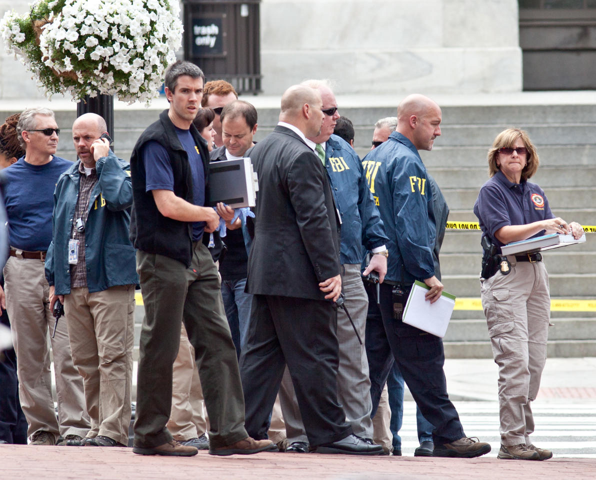 Washington Police and FBI agents gather outside the Family Research Council in Washington, Wednesday, Aug. 15, 2012, after security guard at the lobbying group was been shot in the arm. A police spokeswoman says the shooting happened Wednesday morning at the Family Research Council. Police say one person has been taken into custody. (AP Photo/J. Scott Applewhite)