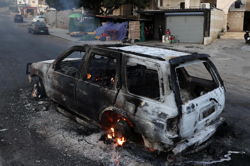 A family looks at a burning car after heavy clashes in the coastal town of Khaldeh, south of Beirut, Lebanon, Sunday, Aug. 1, 2021. At least two people were killed on Sunday south of the Lebanese capital when gunmen opened fire at the funeral of a Hezbollah commander who was killed a day earlier, an official from the group said. (AP Photo/Bilal Hussein)