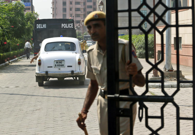 An Indian policemen closes the gate of a court after a van, carrying four men accused in the fatal gang rape of a young woman on a moving New Delhi bus last year, entered the premises in New Delhi, India, Tuesday, Sept. 10, 2013. An Indian court is set to deliver judgment in the Dec. 16 gang rape case that has sparked a national debate about the treatment of women across the country and the inability of law enforcement to protect them. (AP Photo/Saurabh Das)
