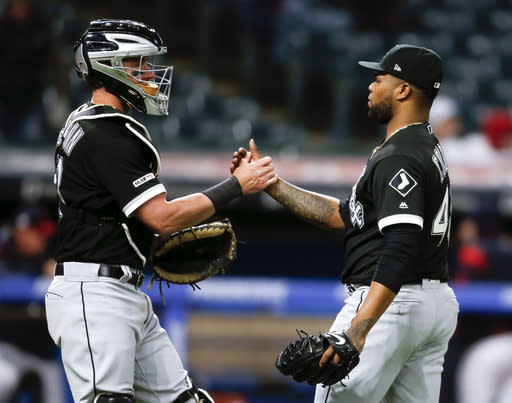 Chicago White Sox relief pitcher Alex Colome, right, and James McCann celebrate a 2-0 victory over the Cleveland Indians in a baseball game, Tuesday, May 7, 2019, in Cleveland. (AP Photo/Ron Schwane)