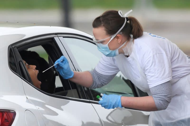 FILE PHOTO: A person is tested at a coronavirus test centre in the car park of Chessington World of Adventures