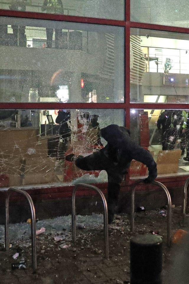 A protester kicks a smashed Bridewell police station window in Bristol