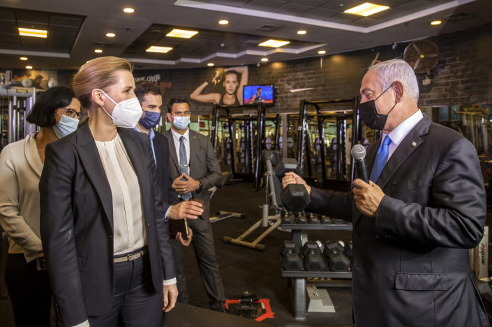 """Israeli Prime Minister Benjamin Netanyahu, holds a barbell as he speaks to Danish Prime Minister Mette Frederiksen, left, during a visit a fitness gym with Austrian Chancellor Sebastian Kurz, to observe how the """"Green Pass,"""" for citizens vaccinated against COVID-19, is used, in Modi'in, Israel, Thursday, March 4, 2021. Frederiksen and Kurz are on a short visit to Israel for to pursue the possibilities for closer cooperation on COVID-19 and vaccines. (Avigail Uzi/Pool via AP)"""