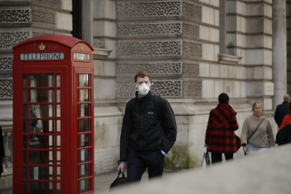 A man wearing a face mask walks past a traditional British red phone box near Parliament Square in central London, Wednesday, March 11, 2020. A British government minister Nadine Dorries, who is a junior Heath minster has tested positive for the coronavirus and is self isolating. For most people, the new coronavirus causes only mild or moderate symptoms, such as fever and cough. For some, especially older adults and people with existing health problems, it can cause more severe illness, including pneumonia. (AP Photo/Matt Dunham)