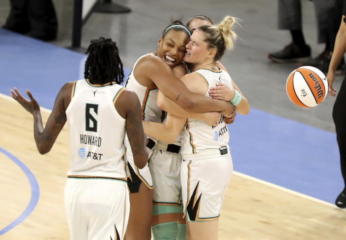 New York Liberty players Betnijah Laney, left center, hugs teammates Sabrina Ionescu and Sami Whitcomb, right, after winning a WNBA basketball game over the Chicago Sky Sunday, May 23, 2021, in Chicago. (AP Photo/Eileen T. Meslar)