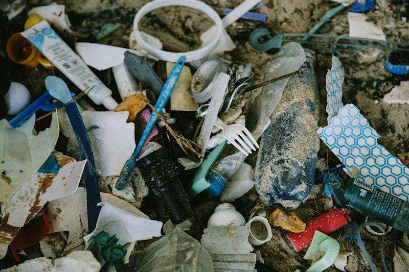 A pile of rubbish including a fork and toothbrush mixed in with sand.