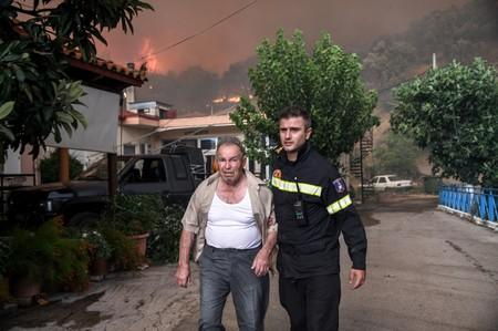A firefighter helps a local as a wildfire burns at the village of Kontodespoti, on the island of Evia