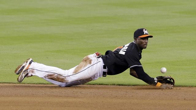 Miami Marlins shortstop Adeiny Hechavarria is unable to field a ground ball by Pittsburgh Pirates' Josh Harrison in the fifth inning of a baseball game in Miami, Saturday, June 14, 2014. (AP Photo/Alan Diaz)