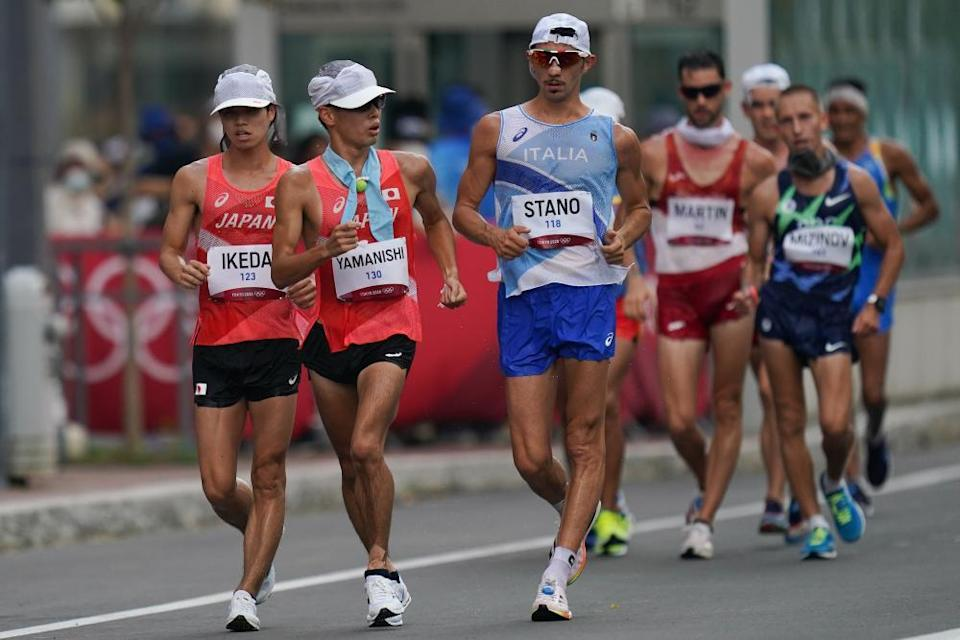 Ikeda Koki (L front) and Yamanishi Toshikazu (C front) of Japan and Massimo Stano of Italy compete during the men's 20km race walk.