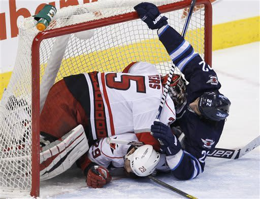 Winnipeg Jets' Chris Thorburn (22) crashes into Carolina Hurricanes goaltender Justin Peters (35) and Tim Wallace (29) during the first period of their NHL hockey game in Winnipeg, Manitoba, Thursday, April 18, 2013. (AP Photo/The Canadian Press, John Woods)