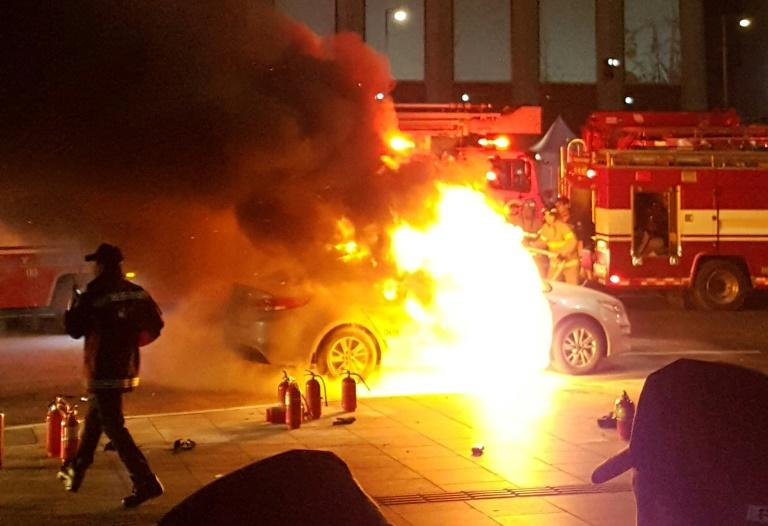 Photo by eyewitness Lee Sang-ho shows a burning taxi as a driver commits suicide near the US embassy in Seoul