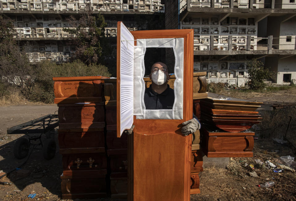 A funeral worker asks for his photo to be taken through one of the used coffins he is moving following cremations at La Recoleta cemetery during the coronavirus pandemic in Santiago, Chile, Monday, April 19, 2021. (AP Photo/Esteban Felix)