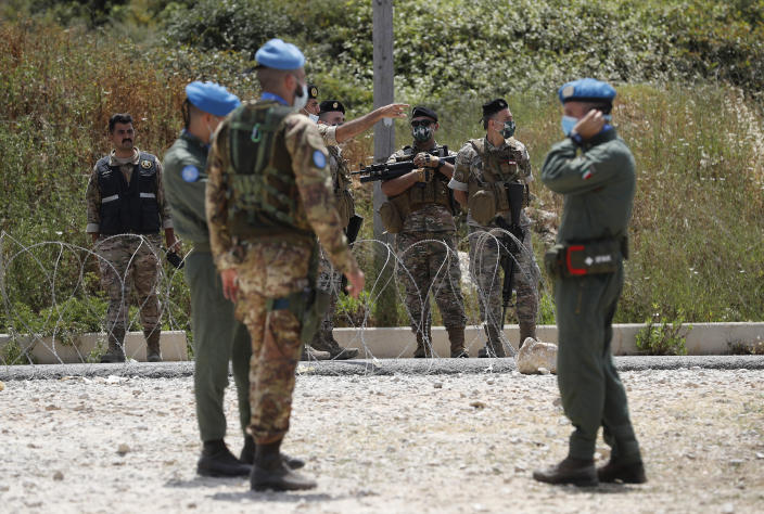 Italian U.N. peacekeepers, with blue berets, and Lebanese soldiers, background, stand guard on a road that leads to a U.N. post along the border known as Ras Naqoura, where Lebanese and Israeli delegations are meeting, in Naqoura, Lebanon, Tuesday, May 4, 2021. Lebanon and Israel have resumed indirect talks with U.S. mediation at the U.N. post over their disputed maritime border after nearly a six-month pause. (AP Photo/Hussein Malla)