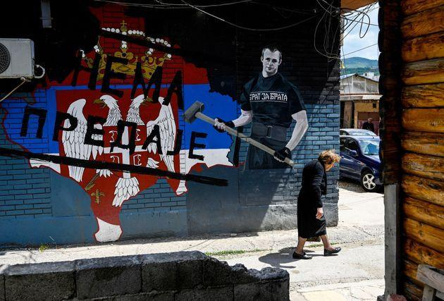 A Kosovo Serb woman walks past a graffiti showing the Serbian flag and reading as
