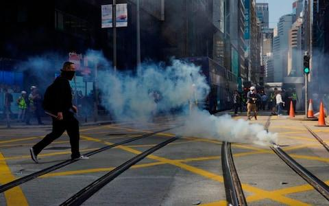 A protester approaches a gas canister deployed in Central district of Hong Kong on Monday - Credit: Vincent Yu/AP