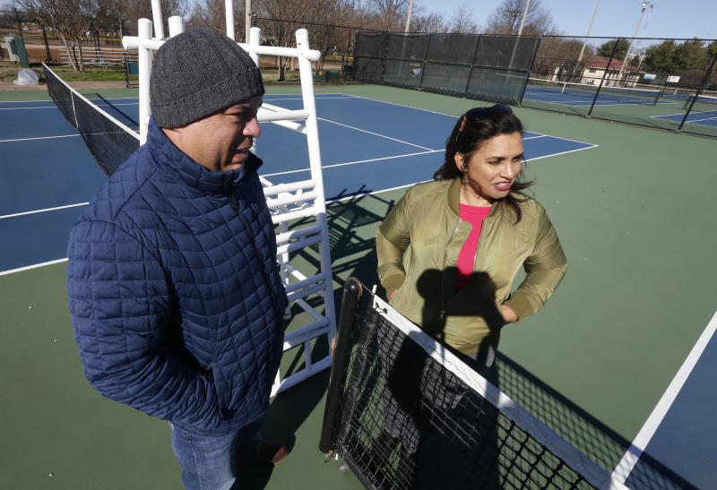In this Jan. 10, 2019, photo David Harris Jr., left, the nephew of Arthur Ashe, and Richmond City Council member, Kim Gray, right, look over the tennis courts on the Boulevard which were tennis star Arthur Ashe was banned from in Richmond, Va. The duo are attempting to get the Boulevard renamed for for tennis great Arthur Ashe. (AP Photo/Steve Helber)