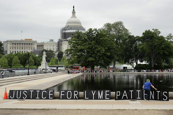 """Bunny Woloszczak of Hurleyville, New York, places a protest sign near the U.S. Capitol Reflecting Pool as part of a """"We The People Rally"""" to bring awareness about Lyme disease May 19, 2016, in Washington, D.C."""