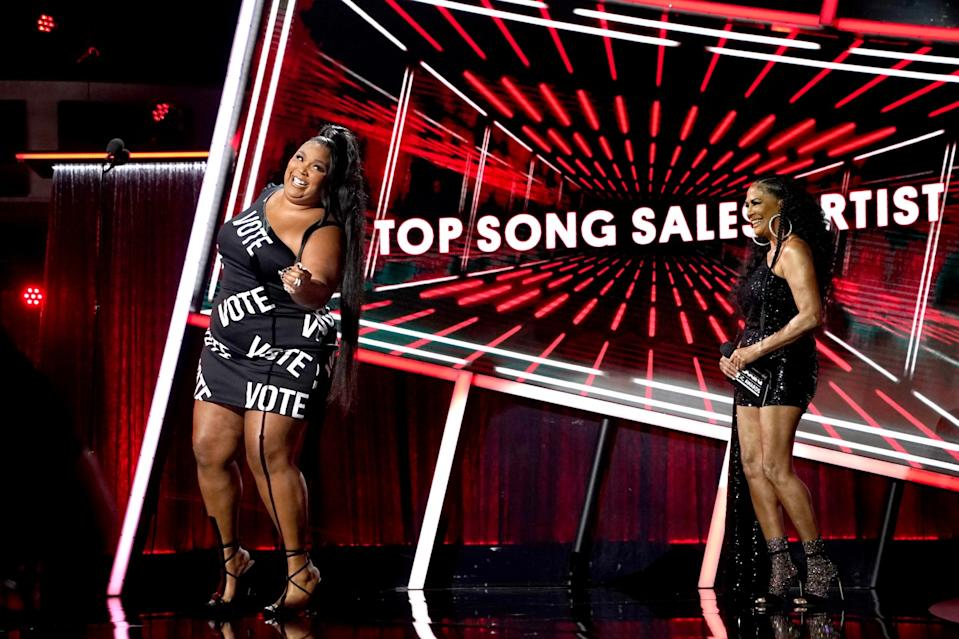 """Lizzo, behind the microphone, wears a dress with the word """"Vote."""""""