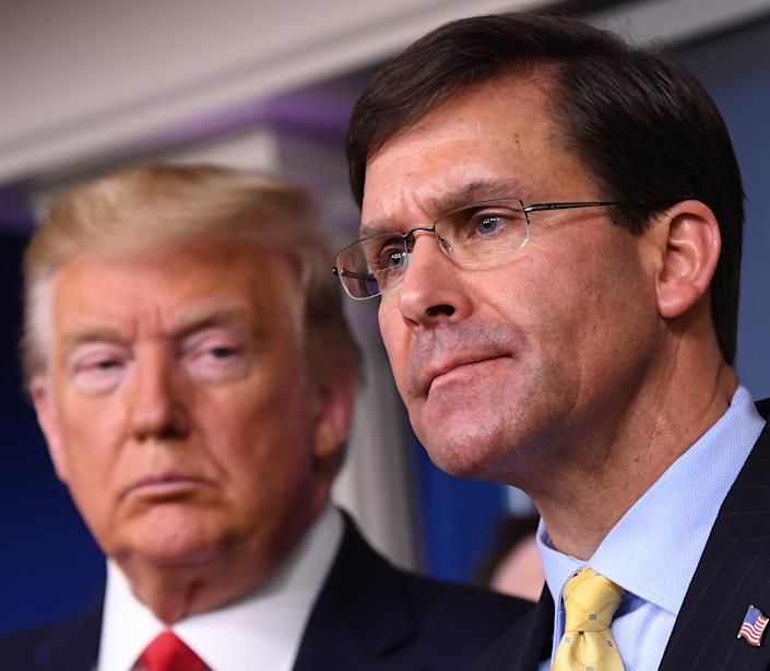 Mark Esper, U.S. secretary of defense, speaks while President Donald Trump, left, listens during a Coronavirus Task Force news conference in the briefing room of the White House in Washington, D.C. in March. (Kevin Dietsch/UPI/Bloomberg via Getty Images)