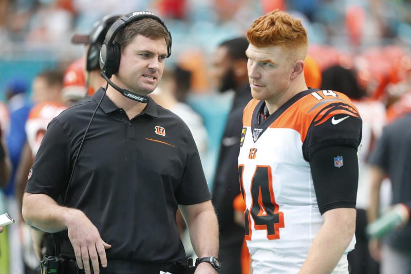 Cincinnati Bengals head coach Zac Taylor, left, talks to quarterback Andy Dalton (14), during the first half at an NFL football game against the Miami Dolphins, Sunday, Dec. 22, 2019, in Miami Gardens, Fla. (AP Photo/Wilfredo Lee)