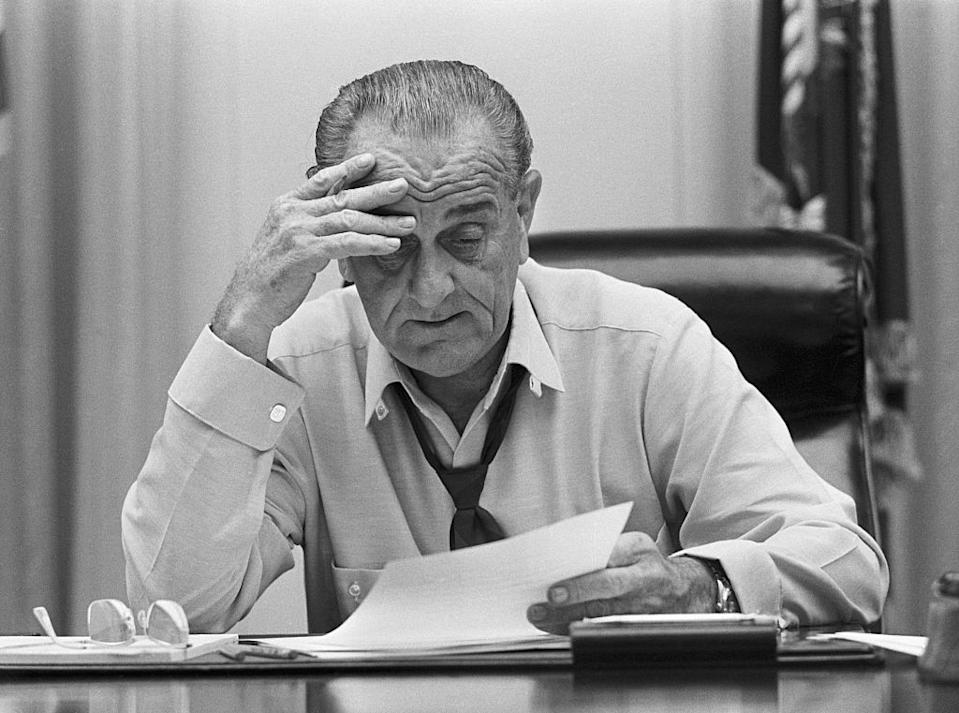 A weary-looking President Johnson looks at documents on his desk in the Cabinet Room of the White House in 1968. He is preparing an address on Vietnam.