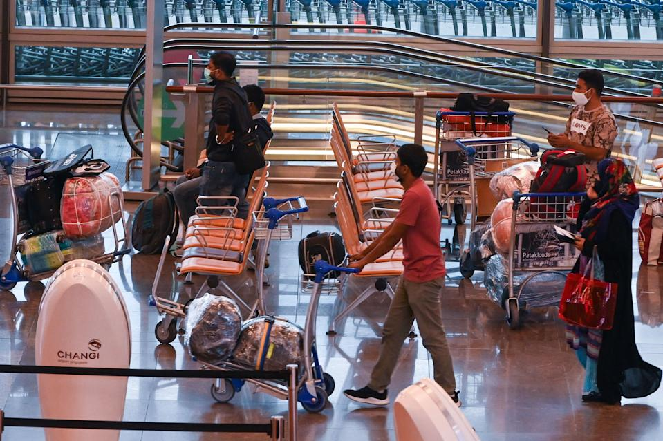 Travellers wait at departure hall before check-in at Changi International Airport in Singapore.