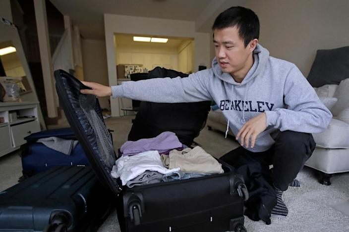 Leo Wang, whose H-1B visa was denied in 2019, packs a suitcase at his home in San Jose, Calif.