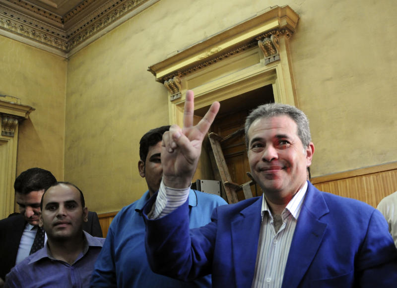 FILE - In this Saturday, Sept. 1, 2012 file photo, Tawfiq Okasha, center, a popular Egyptian TV presenter accused of inciting the killing of the country's new president on air, flashes the victory sign as he arrives for the opening of his trial, in Cairo, Egypt. Police say the trial of Okasha for inciting the murder of Egypt's Islamist president has been detained in connection with a series of allegations, including theft of electrical power and issuing a bounced check. (AP Photo/Mohammed Assad, File)