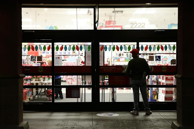 FILE - In this Nov. 28, 2013 file photo, a shopper who declined to give his name waits outside a Kmart store for it to open in Anaheim, Calif. Some retailers, disappointed by sales so far during the holiday shopping season, are staying open for up to 81 hours straight, starting the weekend before Christmas. (AP Photo/Jae C. Hong, File)