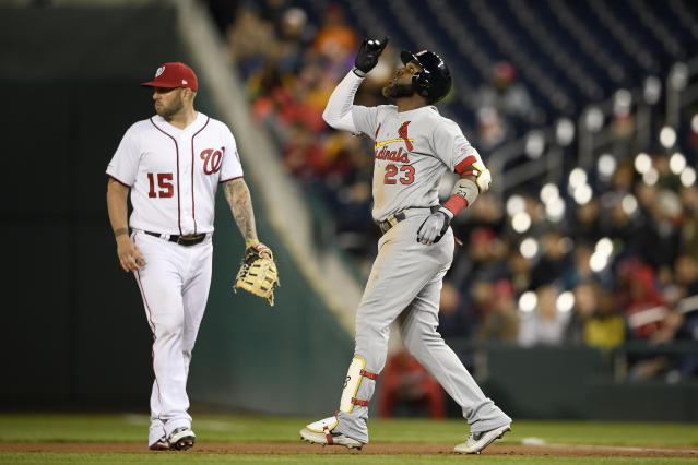 St. Louis Cardinals' Marcell Ozuna (23) reacts next to Washington Nationals first baseman Matt Adams (15) after hitting a single during the seventh inning of a baseball game, Monday, April 29, 2019, in Washington. (AP Photo/Nick Wass)