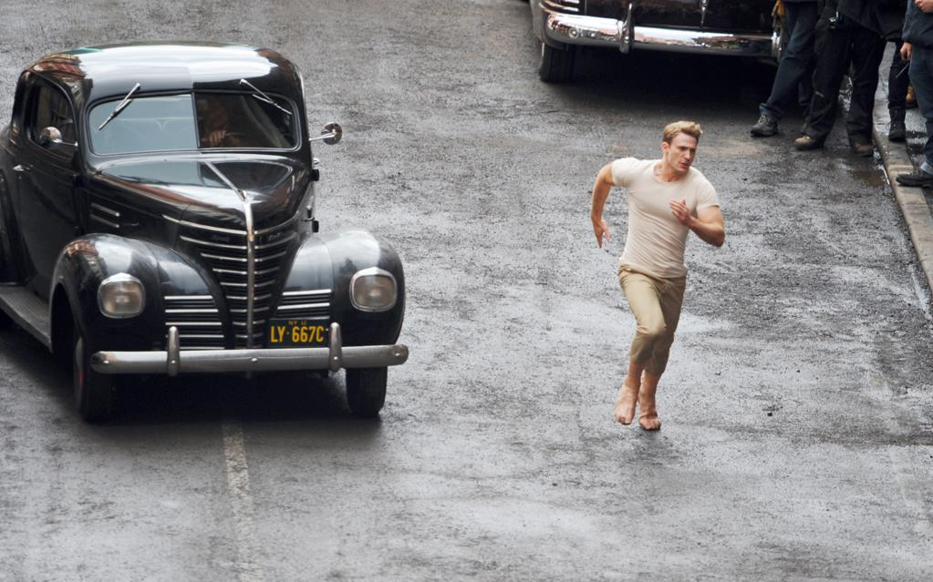 Here Evans is running down a London street -- this is where fake feet come in handy. The movie takes place during World War II, which is why he's flanked by classic cars from the '40s.