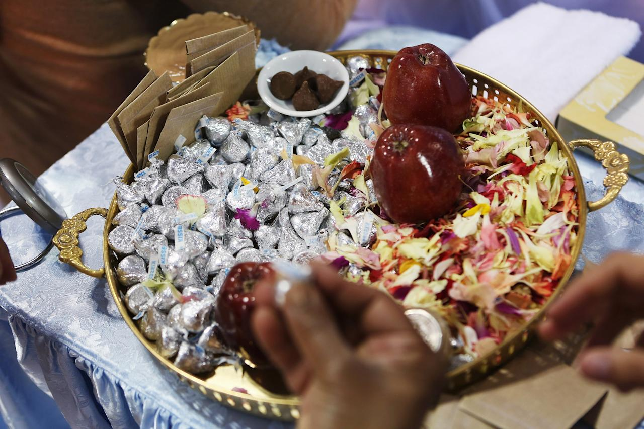 "NEW YORK, NY - JULY 10:  Sweets await distribution to devotees after a blessing by Mata Amritanandamayi, also known as ""The Hugging Saint"" on July 10, 2012 at Javits Center in New York City. The Hindu spiritual leader and guru is on a 10-city U.S. tour, where she is expected to bless thousands of people individually at free public gatherings, known as ""darshan"". Amritanandamayi, 58, from India's southern state of Kerala, is considered a living saint by her followers, who refer to her as ""Amma"" or mother. She has been giving the public ""darshan"" gatherings for 35 years, with the aim of bringing good fortune, well-being and grace to her followers through her embrace. Participants are encouraged to donate to her global charitable organizations, known collectively as ""Embracing the World.""  (Photo by John Moore/Getty Images)"