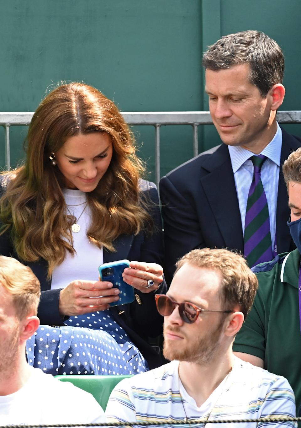 LONDON, ENGLAND - JULY 02: Catherine, Duchess of Cambridge checks her phone while attending Wimbledon Championships Tennis Tournament with Tim Henman at the All England Lawn Tennis and Croquet Club on July 02, 2021 in London, England. (Photo by Karwai Tang/WireImage)