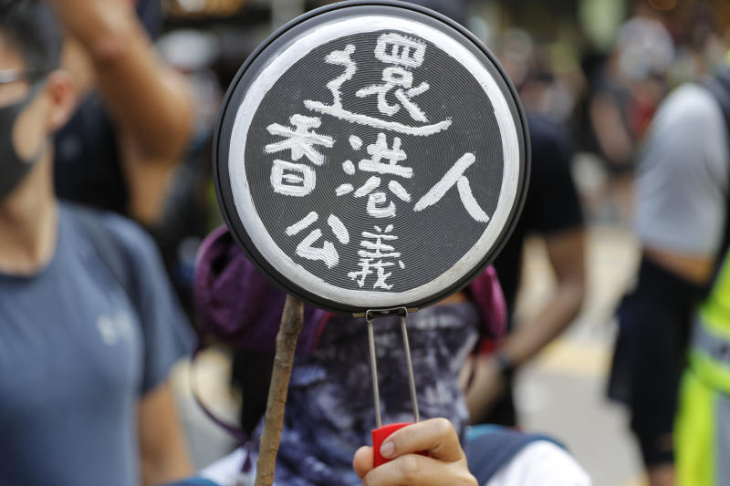 """A protester holds up a cooking pan with the words """"Return Hong Kong People Justice"""" written on the base in Hong Kong on Saturday, Oct. 5, 2019. All subway and trains services are closed in Hong Kong after another night of rampaging violence that a new ban on face masks failed to quell. (AP Photo/Vincent Thian)"""